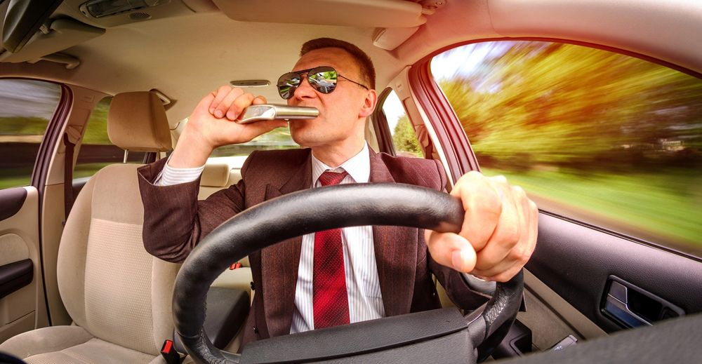 Человек выпивает за рулем из фляжки