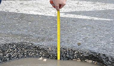 Измерение ямы в асфальте