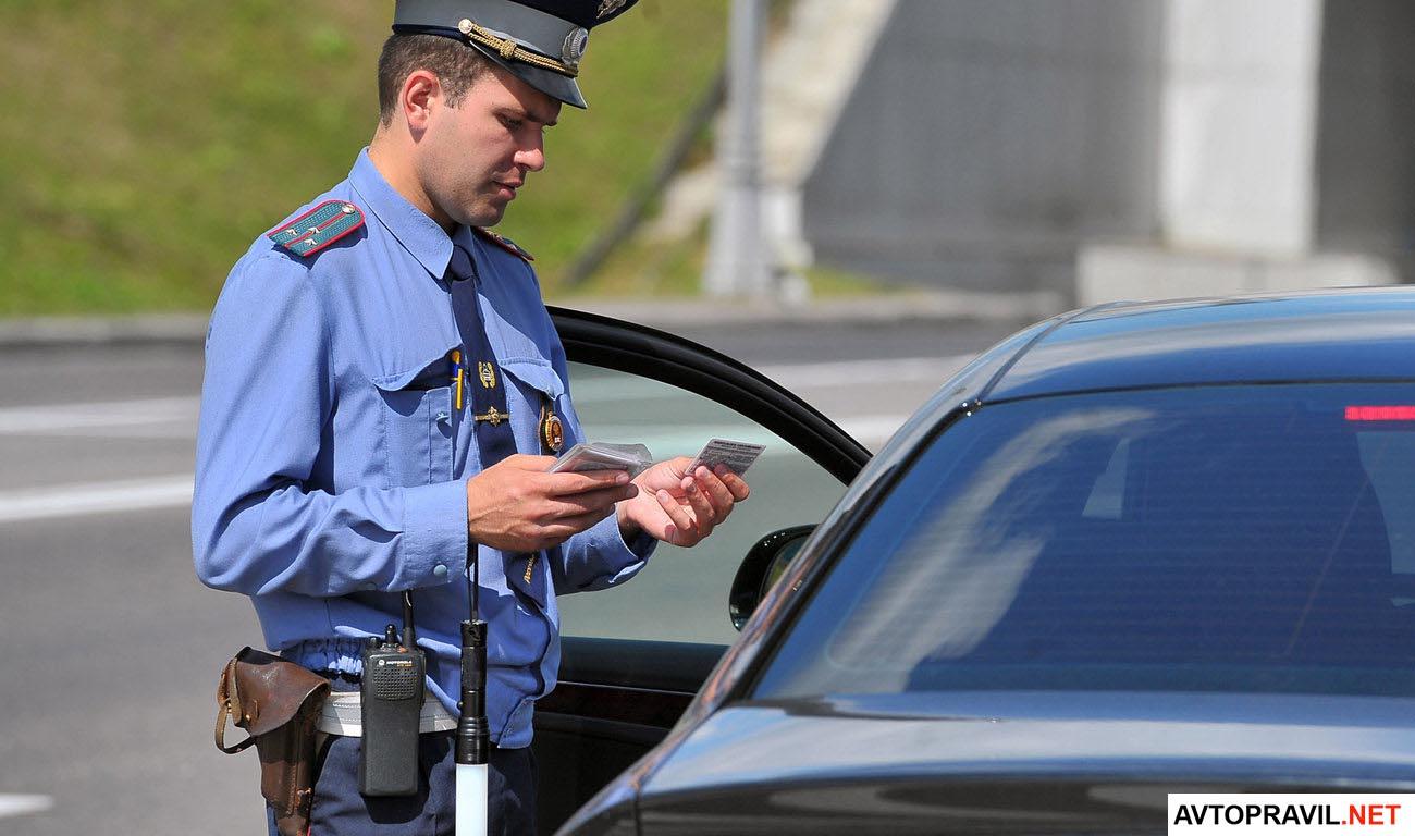 Инспектор ГИБДД проверяющий документы у водителя авто