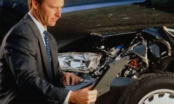 мужчина с ноутом у разбитого крыла автомобиля