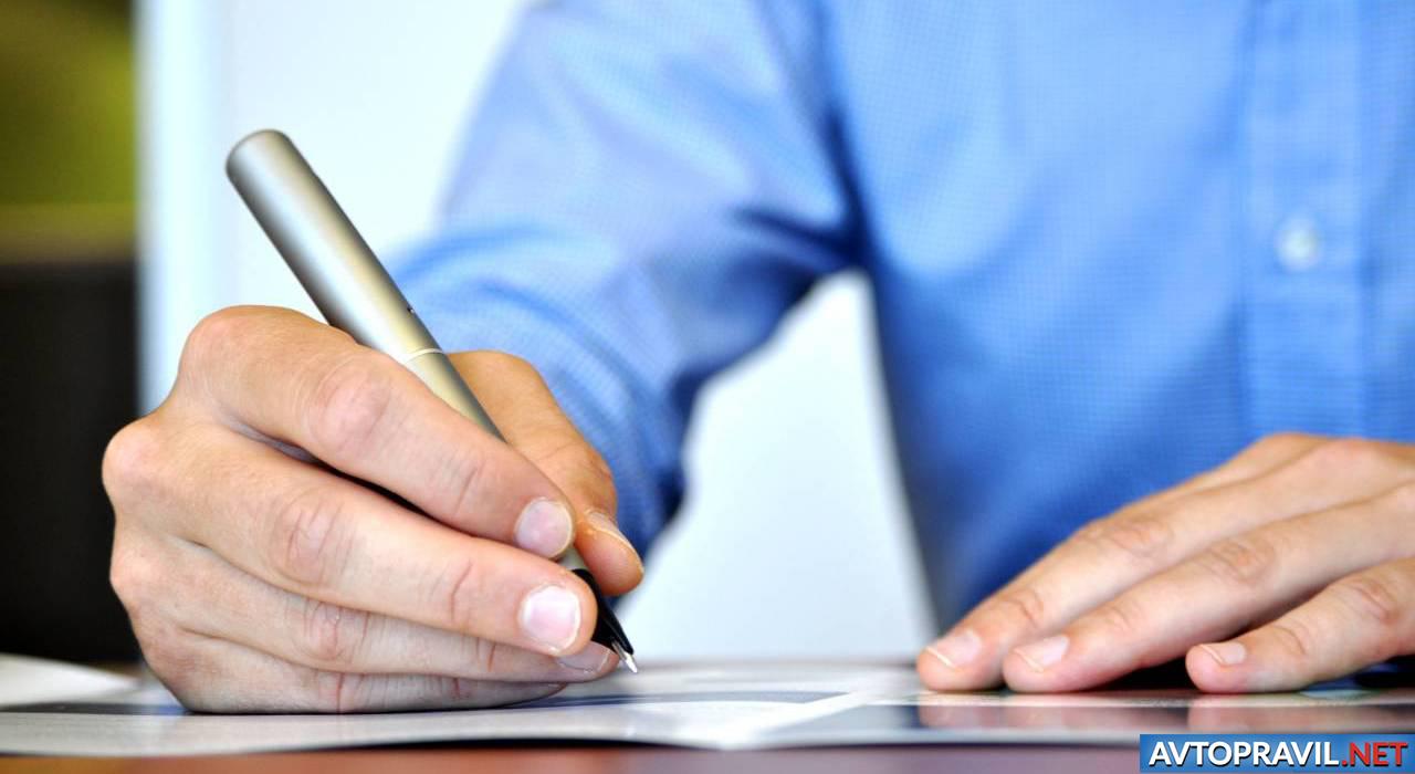 Мужская рука с ручкой над документом