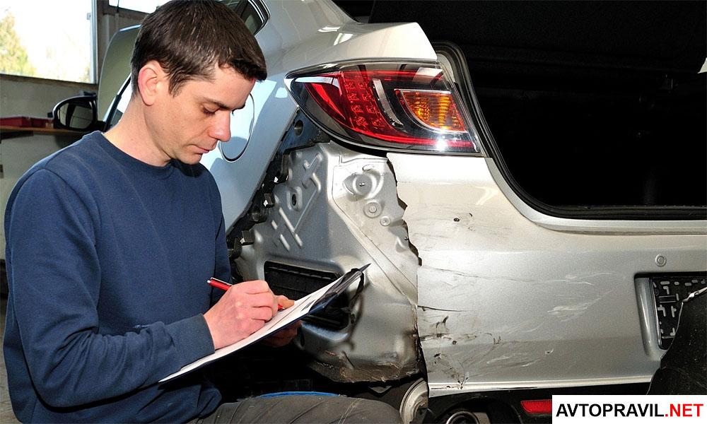 Мужчина, проводящий экспертизу автомобиля после ДТП