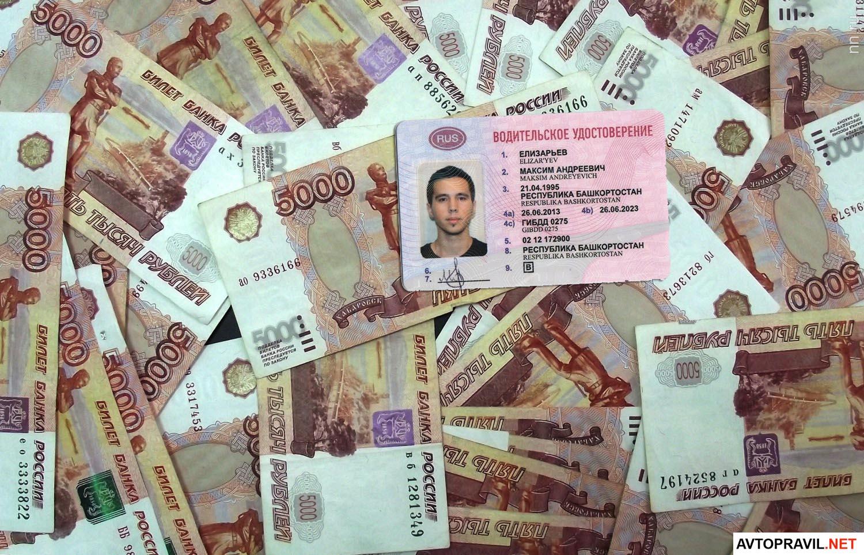 Водительское удостоверение, лежащее на рублях