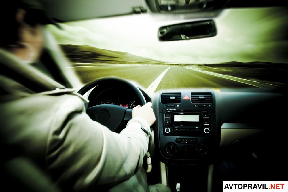 водитель сидящий за рулем быстродвижущейся машины