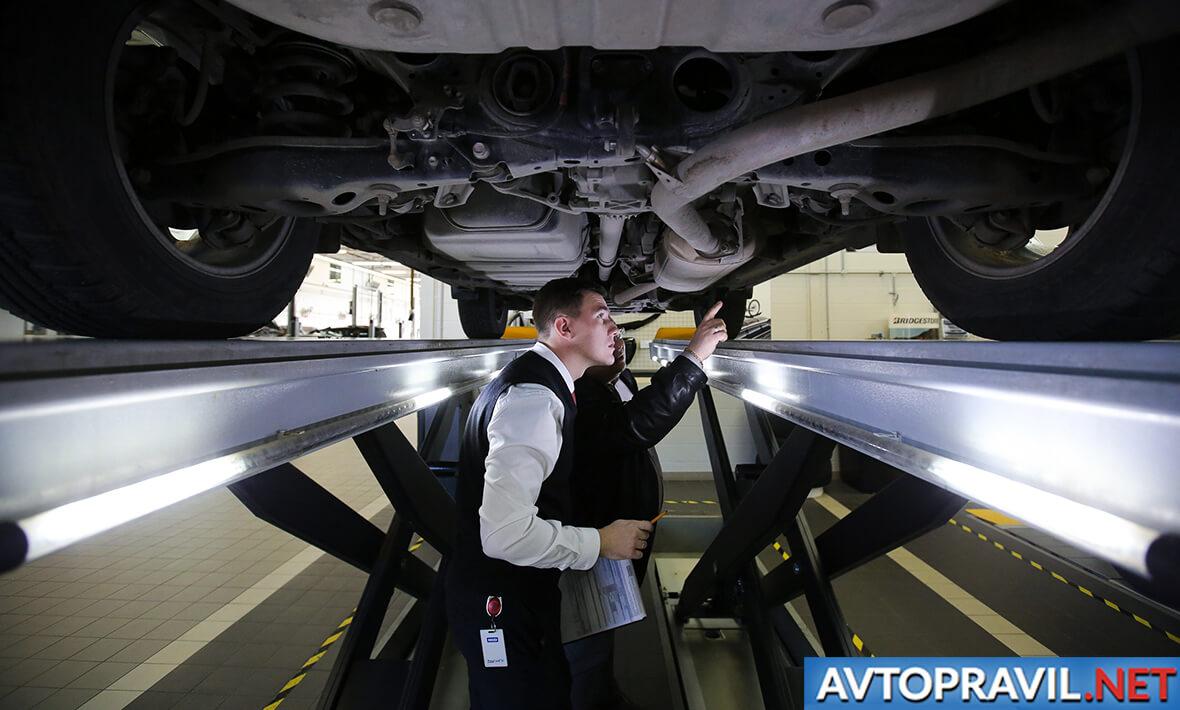 Мужчины, осматривающие днище авто в смотровой яме СТО